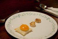 For an amuse-bouche, a fried egg yolk on a pastry biscuit with lightly fried scallops