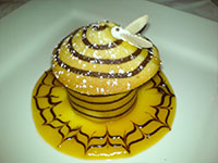 Beehive of chilled honey and Truffle bavarois served in an almond biscuit tuile with apricot coulis and a meringue bee