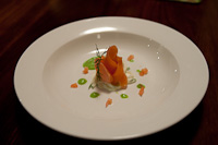 Entree of home-cured salmon, on a bed of cucumber remoulade, decorated with a pea veloute