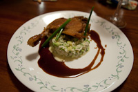 Main course of duck leg confit served with an avocado risotto and a duck jus