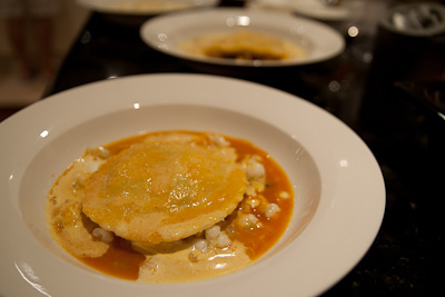 Hand-made ravioli filled with a prawn, carrot and broad bean mousse, surrounded by a prawn and vegetable bouillabaisse
