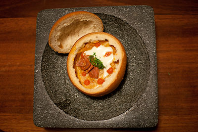 Pumpkin and capsicum royale with goat's cheese and chorizo, served in a bread bowl